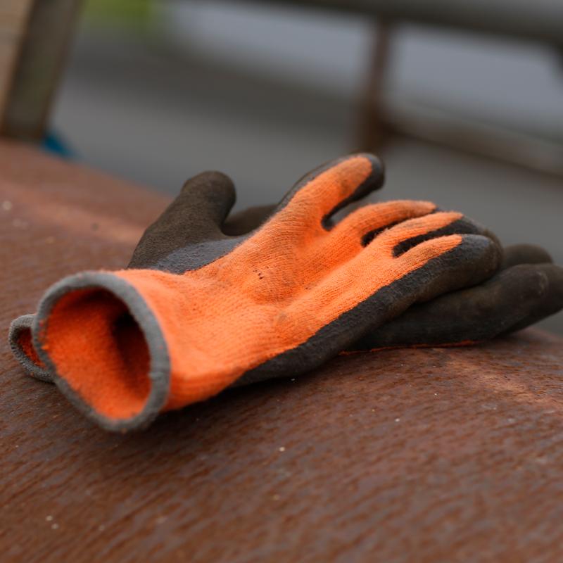Orangea arbetshandskar liggandes på rostigt rör